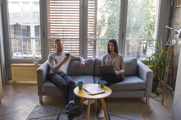 Couple sitting on couch with cell phone and laptop