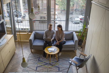 Couple sitting on couch looking at laptop