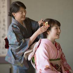 母親に髪飾りをつけてもらう娘