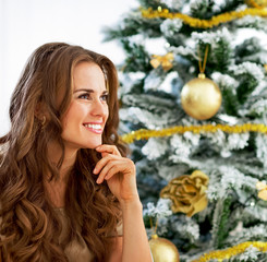 Portrait of thoughtful young woman sitting near christmas tree