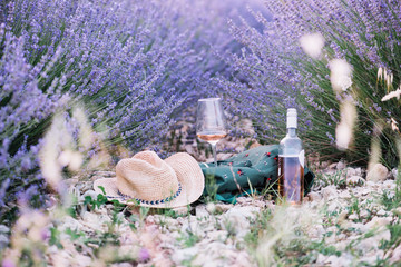Picnic outdoors in lavender fields in Provence, south France. Rose wine in a glass, whole bottle of wine and a travel backpack