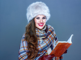 smiling trendy woman isolated on cold blue background with book