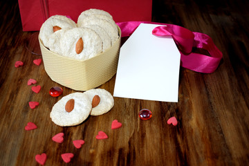 White cookies with almond in a heart-shaped box. Tiny hearts are scattered around. Treats for Valentine's Day