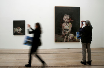 People take pictures of paintings of German artist Baselitz during a media preview of the exhibition 'Baselitz' at the Fondation Beyeler in Riehen