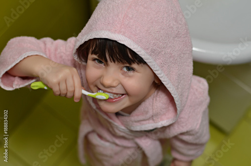 6dc1417f31 Cute little girl in pink bathrobe with hood brushing her teeth in bathroom