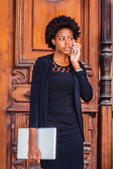 Young African American Businesswoman with afro hairstyle, wearing black fashionable clothes, holding laptop computer, standing by vintage office door in New York, talking on cell phone..