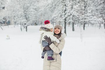 Brunette young women portrait with baby girl, daughter hugs and smiling in snowy park.