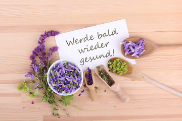 get well soon / greeting card with flowers of sage, thyme and ladys mantle and german Text: get well soon