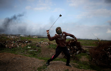 Palestinian demonstrator uses a sling to hurl stones at Israeli troops during clashes, near the border with Israel in the east Gaza Strip