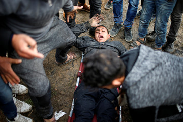 A Palestinian demonstrator reacts after he was injured during clashes with Israeli troops, near the border with Israel in the east Gaza Strip