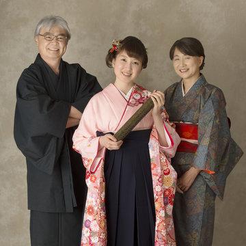 卒業証書を持ち微笑む娘と両親