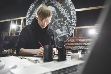 Portrait of a master calligrapher. A tattoo artist makes a sketch while sitting at a table in the Studio