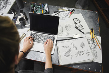 The artist's hand behind the laptop. The hands of a master calligrapher. Tattoo artist the artist makes a sketch, sitting at a table in the Studio top view