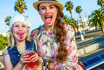 mother and child tourists showing tongues after drinking bright red beverage