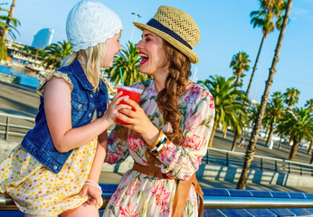 mother and daughter tourists with bright red beverage looking at each other