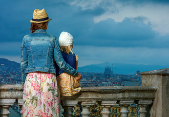 elegant mother and daughter in Barcelona looking into distance