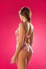 rear view of sexy girl in lingerie set isolated on pink