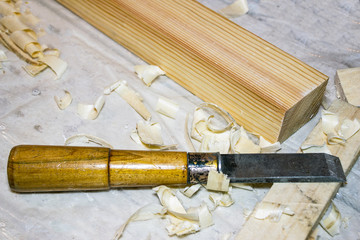 A chisel on the table among the shavings. Nearby there is a wooden bar. Selective focus