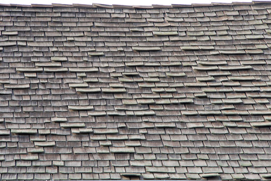 wood shingle roof in poor repair. Wood shingles are thin, tapered pieces of wood primarily used to cover roofs and walls of buildings to protect them from the weather. susceptible to fire and costly