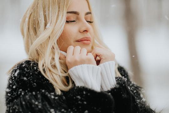 Blonde woman outside in snow winter coat