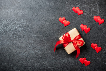 Gift box and red hearts on black background