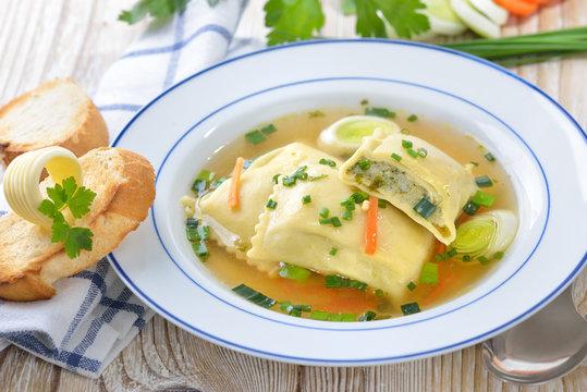 Gemüsebrühe mit deftigen schwäbischen Maultaschen, dazu getoastetes Baguette mit Butterröllchen  - Vegetable soup with Swabian-style ravioli served with butter toast