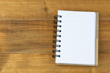 Top view of blank note book on wooden table.