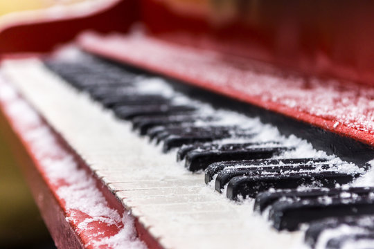 Ancient red piano, keys of which are covered with snow