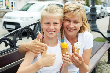 Mother and child eating ice cream in summer street