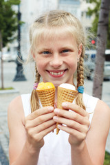 Portrait of 7 years old kid girl eating tasty ice cream in city