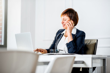 Close-up portrait of an elegant senior businesswoman dressed in the suit talking with phone sitting at the workplace with laptop and documents