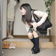 玄関で靴を履く女子学生