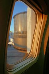 Blick aus einem Flugzeugfenster mit Regentropfen auf eine Passagierbrücke im Morgenlicht