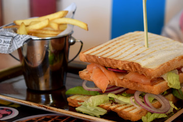 Sandwich with salmon, vegetables and bucket with french fries on a plate