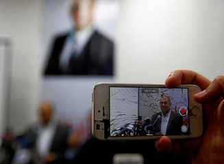 Journalist uses his mobile phone to shoot a video of Egyptian human rights lawyer and opposition leader Khaled Ali during a news conference about the upcoming 2018 presidential elections, in Cairo