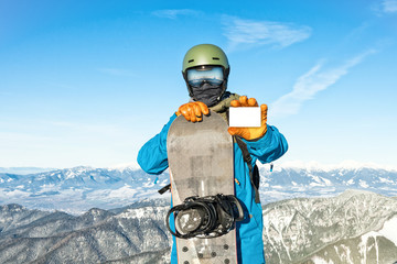 Young snowboarder holding blank ski-pass with beautiful mountains on background