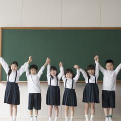 黒板の前に並び手をつなぐ小学生