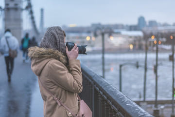 Young woman photographed hipster city with bridge