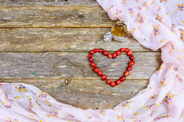 Red wooden beads laid out the shape of a heart on an old wooden table