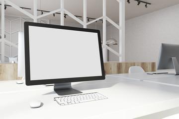 White desktop screen on an office table side