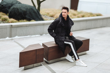 Modern outfit. Fashionable man sit on the bench and look around. Autumn and winter clothing style. Jacket with white sneakers.