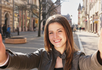 young girl make a selfy on the street in spring