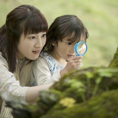 虫眼鏡を持ち観察をする親子