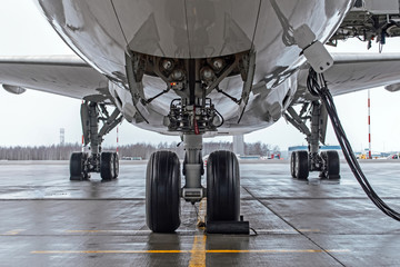 Tuinposter Vliegtuig Landing gear and aircraft wheels parked at the airport, with basic power supply.