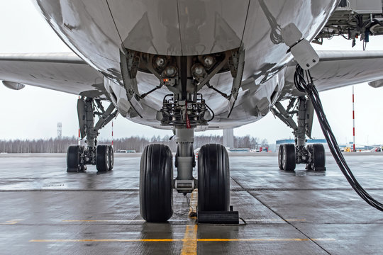 Landing gear and aircraft wheels parked at the airport, with basic power supply.