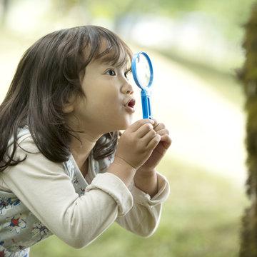 虫眼鏡を持ち観察をする女の子