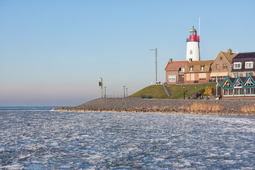 Seascape Dutch fishing village Urk in winter with frozen sea and view at the lighthouse