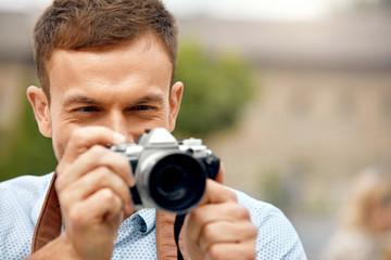 Male Photographer Taking Photos On Camera On Street