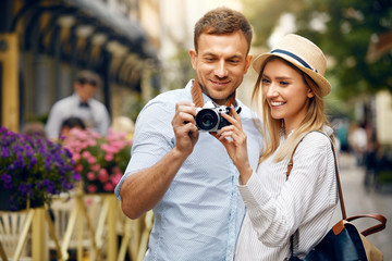 Traveling Couple Taking Photos With Camera In City Street.