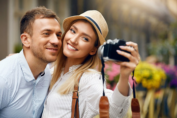 Beautiful Couple Taking Photos With Camera On Street.